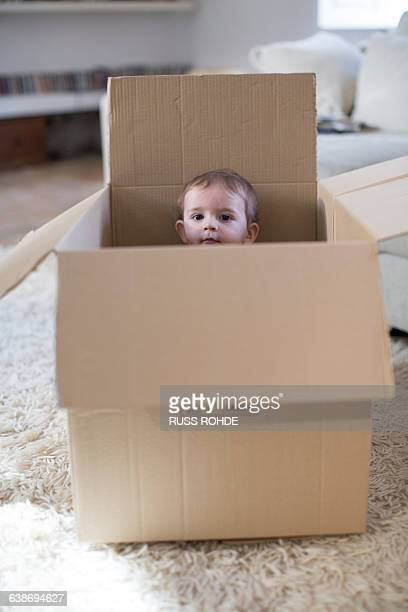 Baby boy in cardboard box peeking out