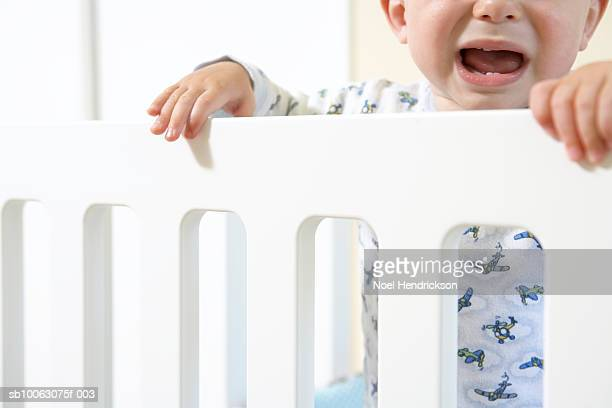 Baby boy (12-15 months) in cot, crying, close-up