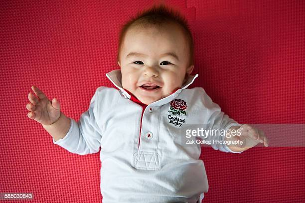 Baby boy in England rugby shirt on red background