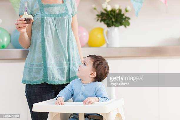 Baby boy in high chair and looking up and mother with birthday cupcake