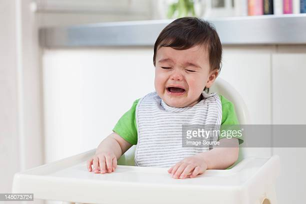 Baby boy in high chair, crying