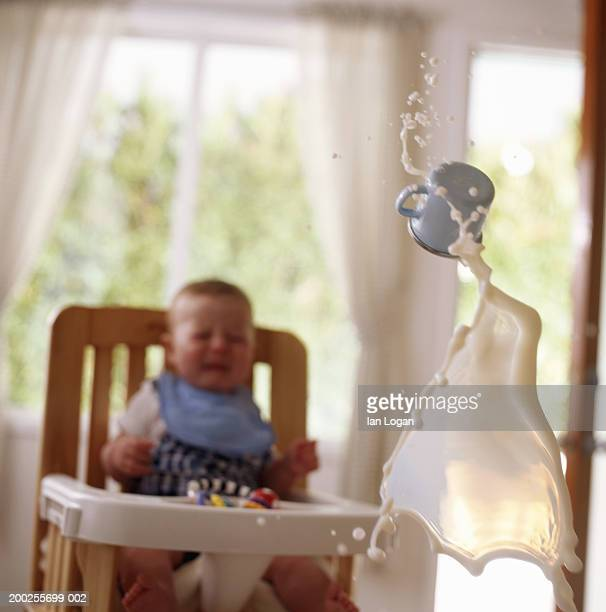 Baby boy (6-9 months) in high chair, cup of milk flying in air