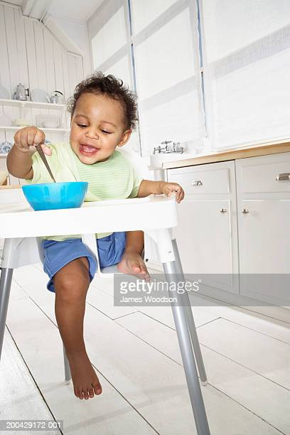 Baby boy (18-24 months) in high chair dipping spoon in bowl