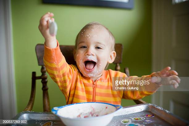 Baby boy (15-18 months) in high chair, face covered with food, smiling