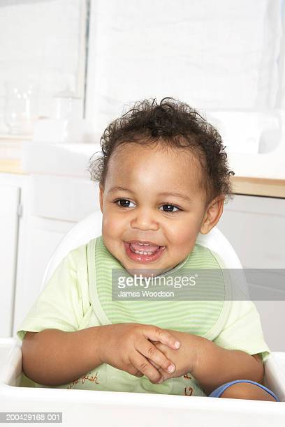 Baby boy (18-24 months) in high chair, hands clasped, smiling
