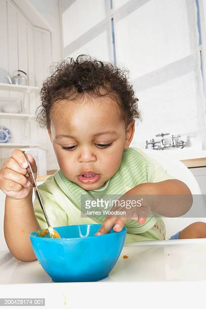 Baby boy (18-24 months) in high chair holding spoon looking in bowl