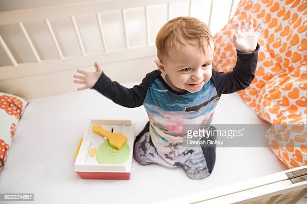 Baby boy in his crib with a toy record player