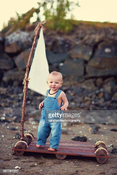 baby boy in overalls on raft