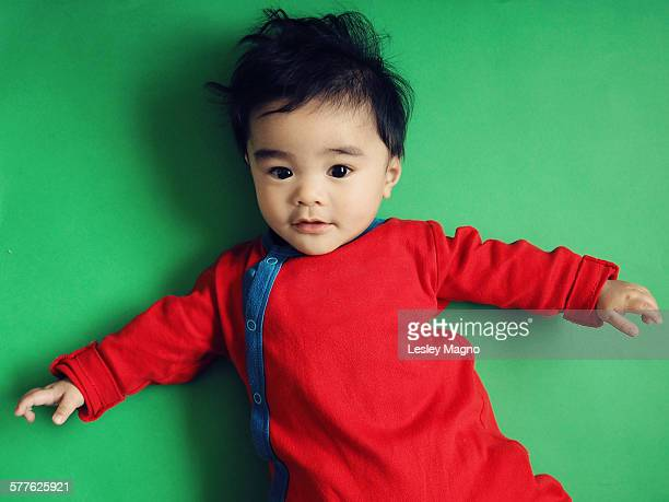 Baby boy in red clothes against green background