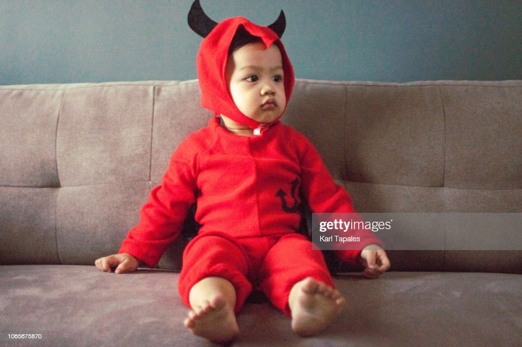 A baby boy in red devil's costume with tail and horns : Stock Photo