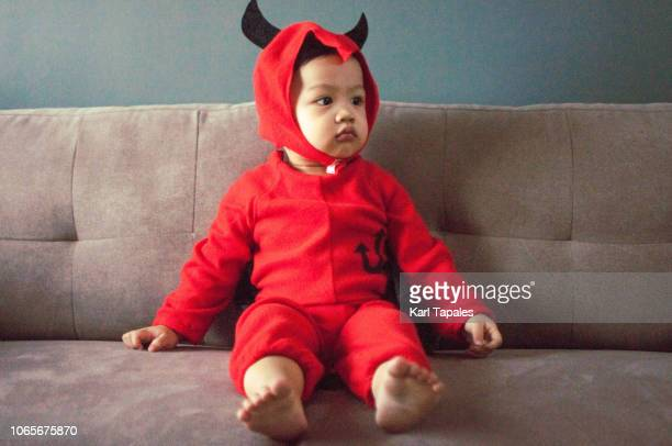a baby boy in red devil's costume with tail and horns - devil costume stockfoto's en -beelden