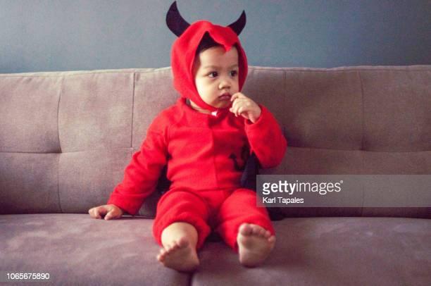 a baby boy in red devil's costume with tail and horns - disfraz de diablo fotografías e imágenes de stock