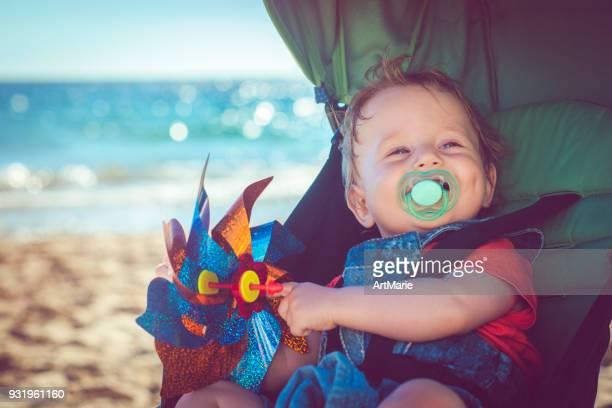 Baby Junge im Kinderwagen am Strand