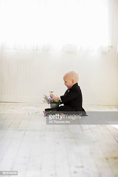 Baby boy in tuxedo planting flowers in pot