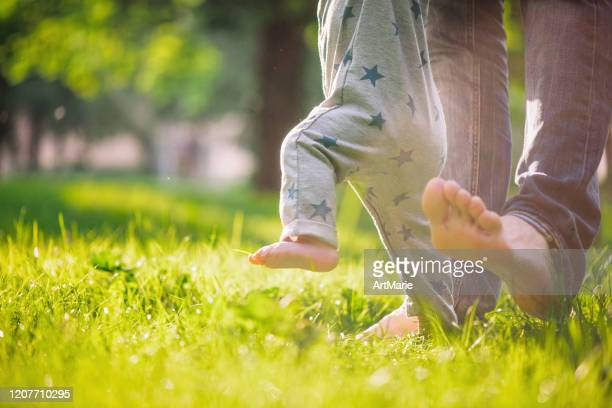 baby boy is happy with his first steps supported by his father on a summer meadow - barefoot stock pictures, royalty-free photos & images