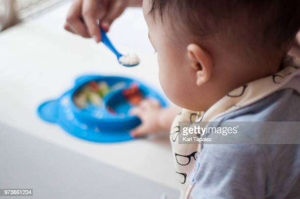 a baby boy is learning to eat with his mother - daily life in philippines stock pictures, royalty-free photos & images