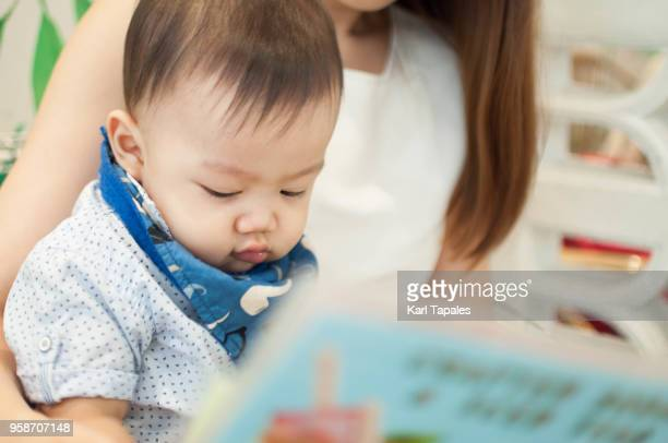 A baby boy is reading a book with his mother