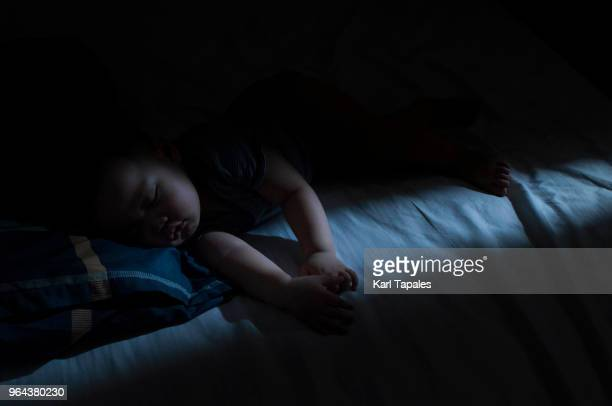 a baby boy is sleeping at night - nursery bedroom stock pictures, royalty-free photos & images