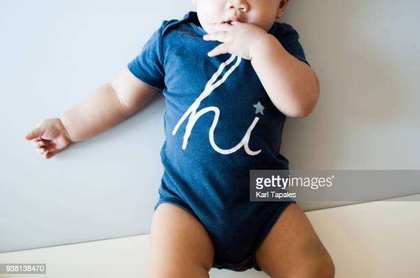 A baby boy is wearing a blue shirt with word hi on it