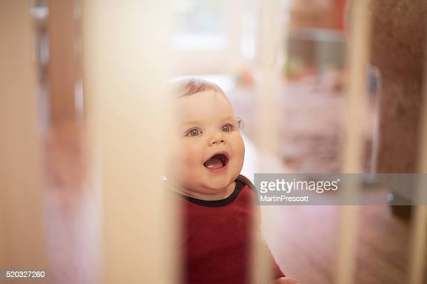 Baby boy laughing behind baby safety gate