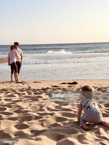 baby boy looking at couple embracing at beach against clear sky - babyhood stock pictures, royalty-free photos & images