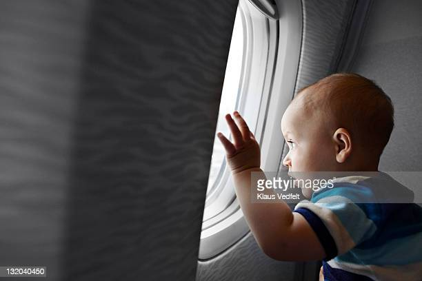 baby boy looking fascinated out of airplane window - one baby boy only stock pictures, royalty-free photos & images