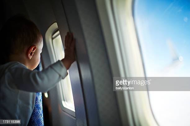 Baby boy looking out airplane window