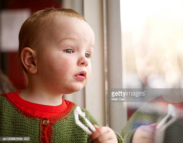baby boy (18-23 months) looking out of window - 18 23 months stock pictures, royalty-free photos & images