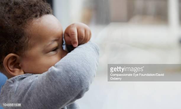 Baby boy looking through window