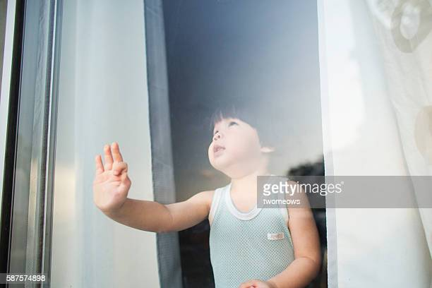 baby boy looking through window - chubby boy stock photos and pictures