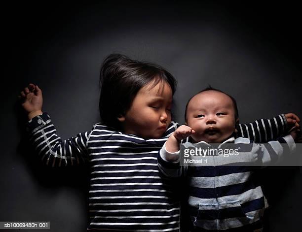 baby boy (0-1 months) lying by sleeping girl (2-3 years) in studio - 0 1 mes fotografías e imágenes de stock
