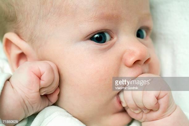 Baby boy lying down and sucking hand