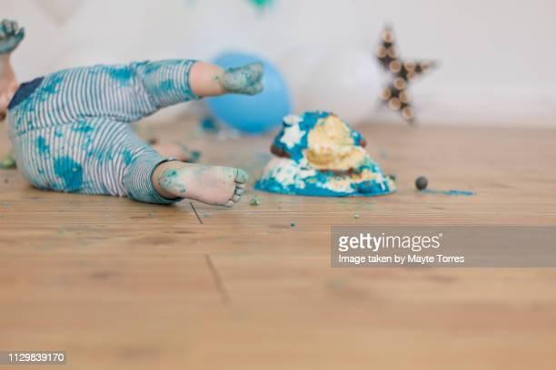 baby boy lying down next to cake - sugar baby imagens e fotografias de stock