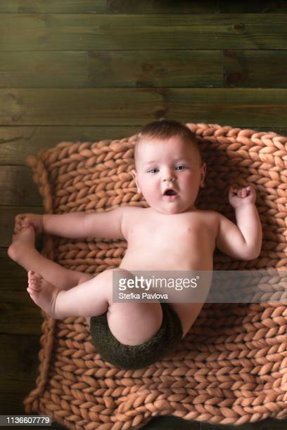 baby boy lying down on his back with legs up touching foot - bare breasted babes stock pictures, royalty-free photos & images