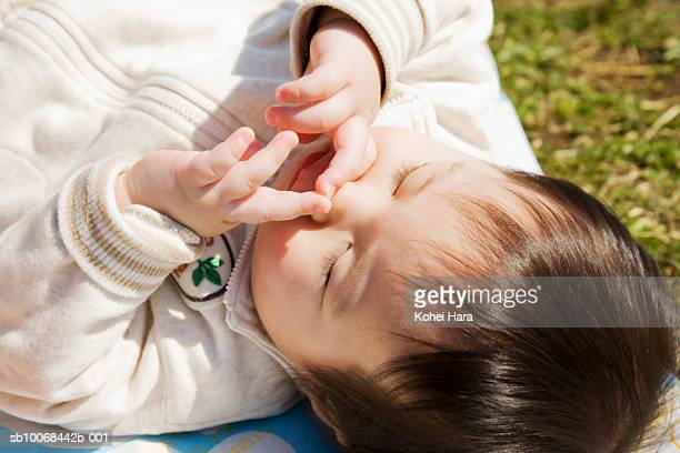 Baby boy (6-11 months) lying down picking nose on grass