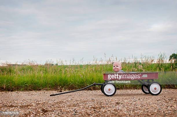 Baby boy lying in red wagon