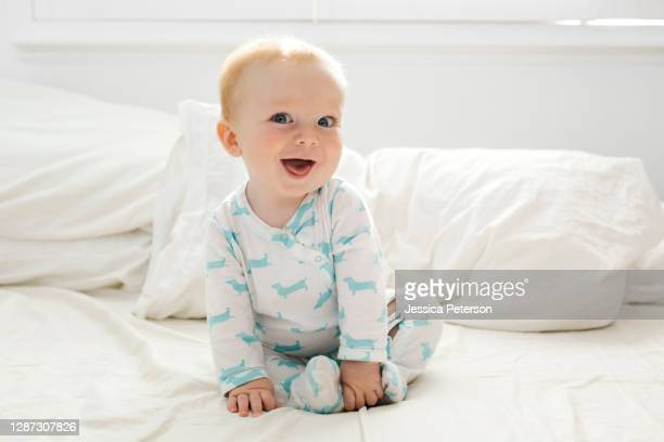 baby boy (6-11 months) lying on bed - baby stock pictures, royalty-free photos & images