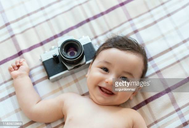 baby boy lying on bed with slr camera - baby boys stock pictures, royalty-free photos & images