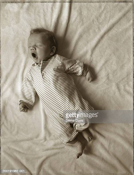 baby boy (0-3 months) lying on bed, yawning (toned b&w) - 0 1 months stock pictures, royalty-free photos & images