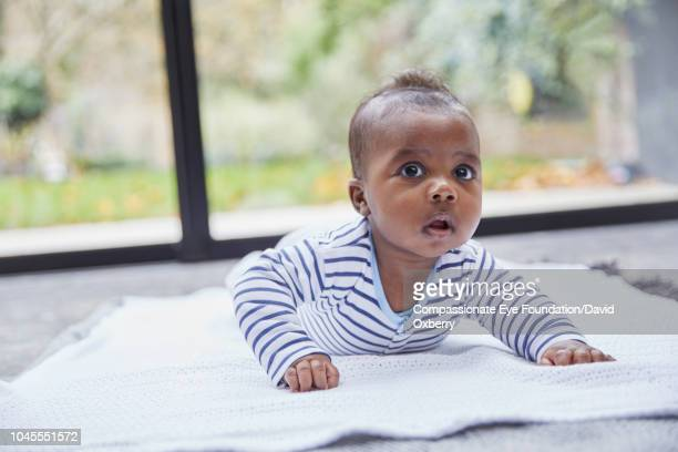Baby boy lying on rug by window