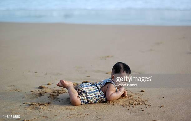 Baby boy lying on sand