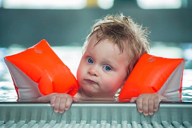 Baby boy makes face in a swiming pool