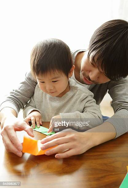 Baby boy making origami with father