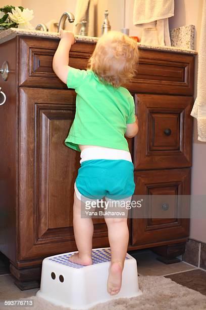 baby boy on a stool near the bathroom vanity - junge in unterhose stock-fotos und bilder