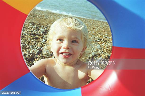Baby boy (18-21 months) on beach, view through centre of inflatable ring