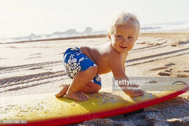 Baby boy (9-12 months) on surfboard at beach