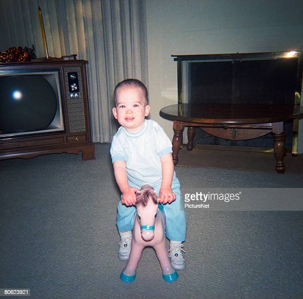 Baby boy on toy horse in living room