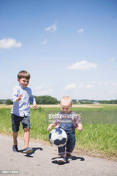 Baby boy playing football with his brother on meadow in the countryside, Bavaria, Germany