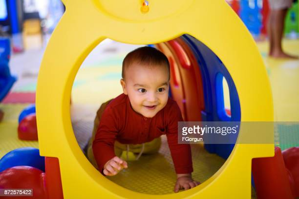 Baby boy playing in a tunnel tube