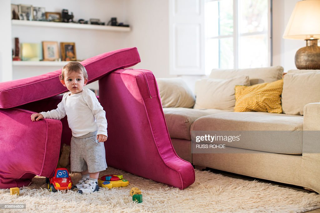 Baby boy playing in fort made from sofa cushions : Stock Photo